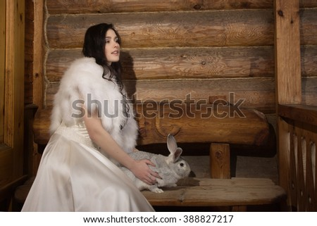Young woman bride smiling and holding rabbit on a porch of a wooden house