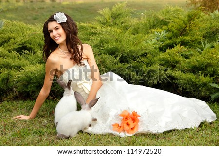 Young woman bride smiling playing with cute rabbit over park summer nature outdoor, Alice in Wonderland - stock photo