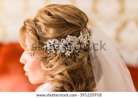 young woman bride with beautiful hairstyle and stylish hair accessory, rear view