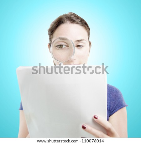 Young woman browsing a document with a magnifying glass over light blue gradient background - stock photo