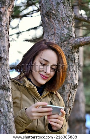 Young woman browsing smart phone while sitting on a tree in autumn  - stock photo