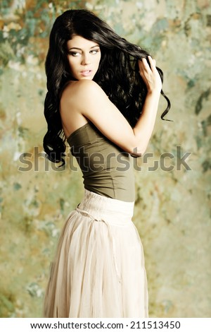 Young woman brunette shows her long healthy beautiful hair - stock photo
