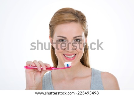 young woman brushes her teeth with white paste
