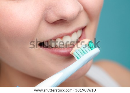 Young woman brushing cleaning teeth. Girl holds toothbrush with toothpaste on it. Oral hygiene.
