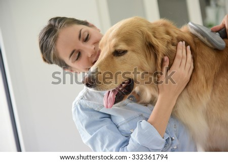 Young woman brushing her dog's hair