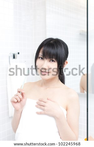 young woman brushing her teeth in the bathroom - stock photo