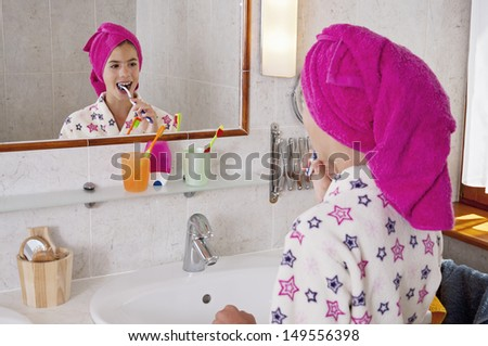 Young woman brushing teeth in bath robe with towel on head in bright bathroom