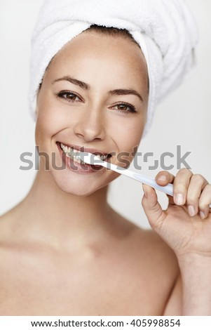 Young woman brushing teeth, portrait