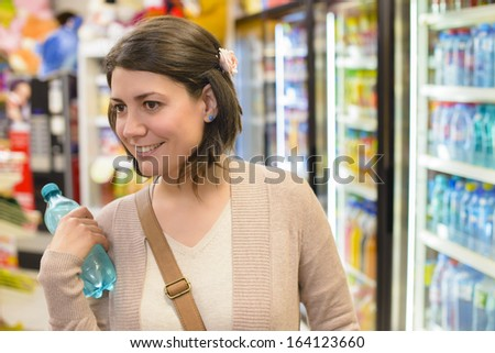 Young woman buying a bottle of water from a store - stock photo