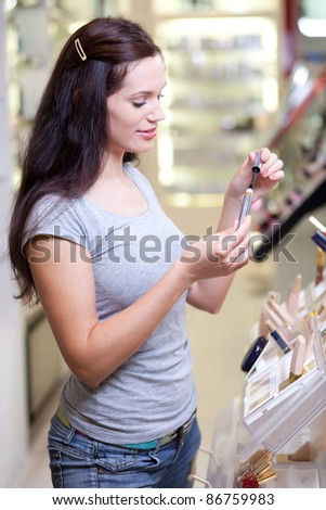 Young woman buying a mascara. Shallow DOF. - stock photo