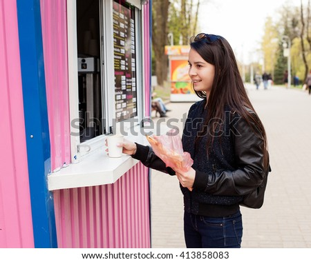 Young woman buying coffee in a street shop in the city park