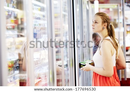 Young woman buying dairy or refrigerated groceries at the supermarket in the refrigerated section opening glass door of the fridge - stock photo