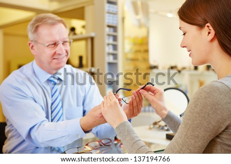 Young woman buying glasses at senior optician