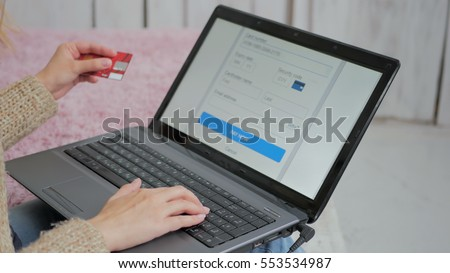 Young woman buying goods from the internet and entering number security code from credit card on laptop. Online, technology and internet concept.