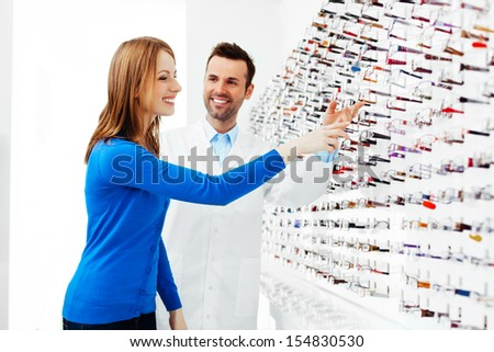 Young woman buying new glasses at optician store.