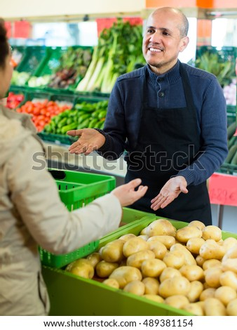 Young woman buying new potatoes from local distributor in grocery