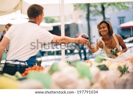 Young woman buying vegetables at farmers market - stock photo