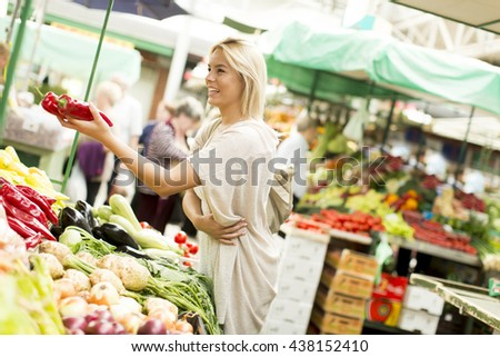 Young woman buying vegetables at the market
