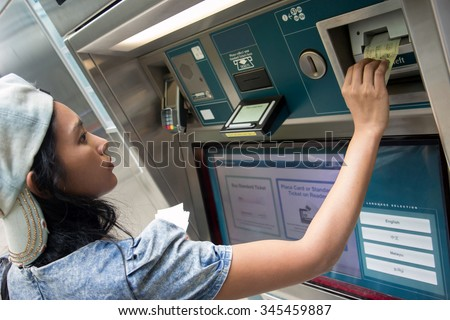 Young woman buys a ticket vending machine. Purchase tickets in public transport ticket vending machine. Payment ticket subway vending machine. Asian tourist buys a ticket for train at vending machine.
