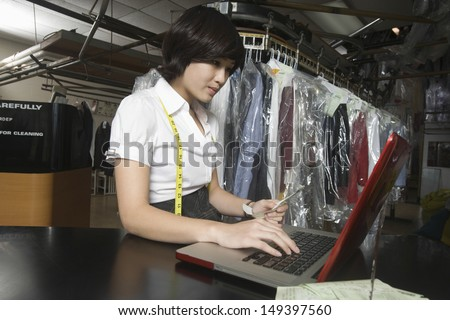 Young woman calculating bill with laptop in laundry - stock photo