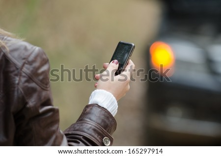 Young woman calling for help next to the car with hazard lights. Close-up of woman's arm holding a mobile phone. Symbol of car accident, car repair and maintenance or other situations related with car - stock photo