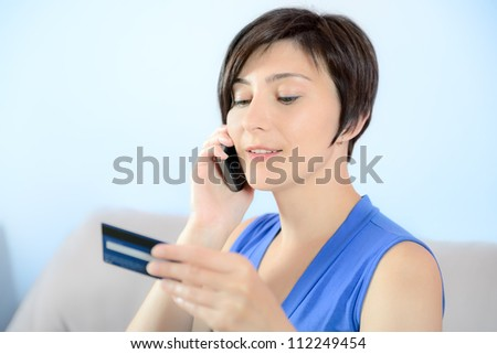 Young woman calling on mobile phone and holding a credit card. - stock photo