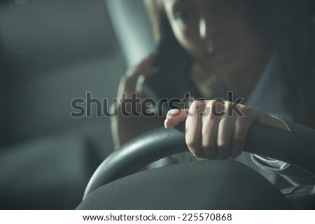 Young woman calling on the phone while driving late at night. - stock photo