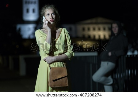 Young woman calling to somebody at night - stock photo