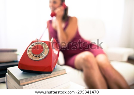Young woman calling with a red retro phone at home, talking and laughing - stock photo