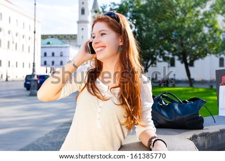 Young woman calls with a smartphone or a mobile phone in a park in the summer - stock photo