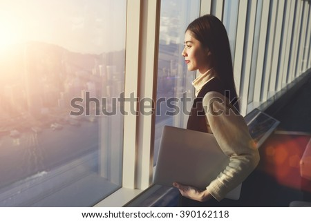 Young woman candidate is holding laptop computer, while standing in office interior and looking out of big window with city view. Female manager with net-book in hand ponder about new business project - stock photo