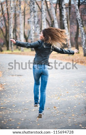 young woman capers like a kid in the autumn park - stock photo
