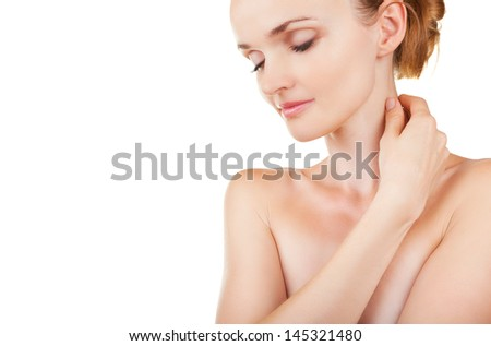 Young woman cares for face skin with closed eyes isolated on white background