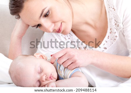 Young woman caressing her newborn baby who is asleep - stock photo