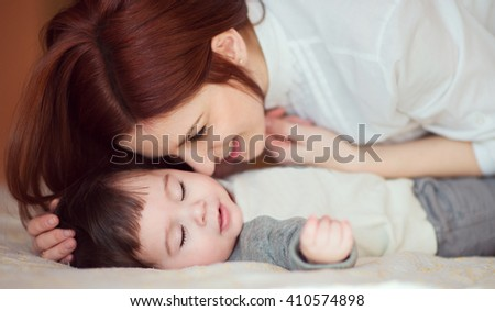 Young woman caressing her newborn baby who is asleep. Sweet moment - stock photo