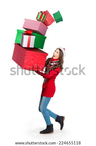 Young woman carrying a pile of collapsing presents - stock photo