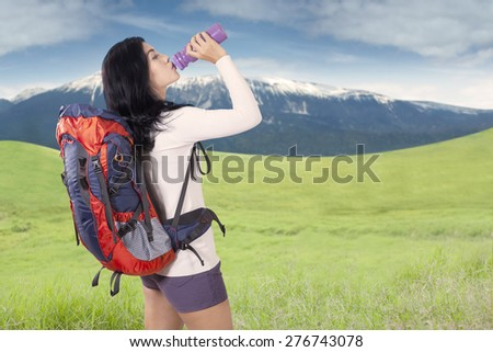 Young woman carrying backpack for hiking and drinking fresh water with bottle on the mountain - stock photo
