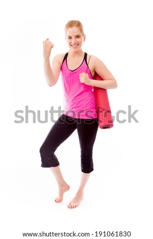Young woman carrying exercising mat and celebrating success - stock photo