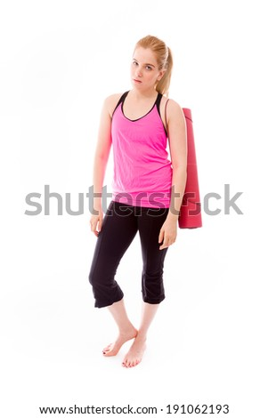 Young woman carrying exercising mat and looking serious