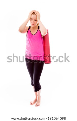 Young woman carrying exercising mat looking depressed - stock photo