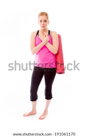 Young woman carrying exercising mat shivering in cold