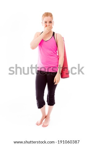 Young woman carrying exercising mat with hand over her mouth