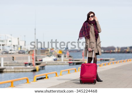 Young woman carrying luggage and calling by mobile phone. - stock photo