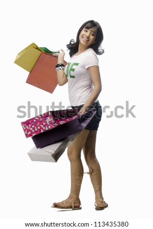 Young woman carrying shopping bags - stock photo