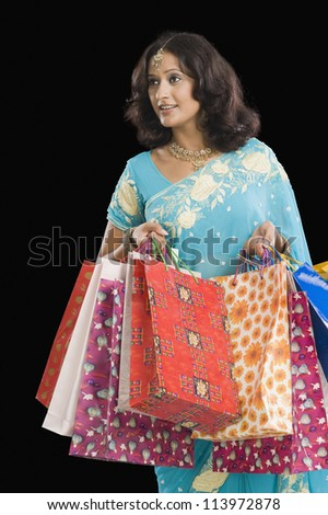 Young woman carrying shopping bags and smiling - stock photo
