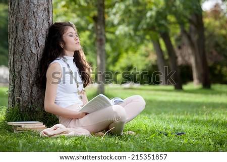 Young woman caucasian asian dreaming laying against a tree sitting in the grass with a book in hands