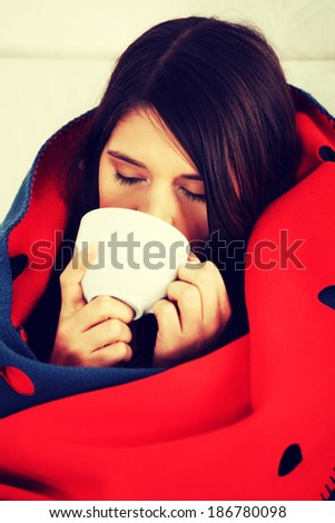 Young woman caught cold, wrapped up in blanket, drinking something hot from cup.  - stock photo