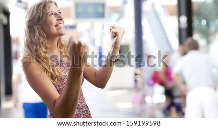 young woman celebrating her success in a shopping center - stock photo