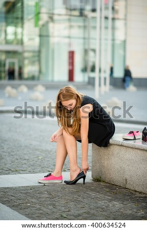 Young woman changes shoes on street high heels instead of sneakers - stock photo