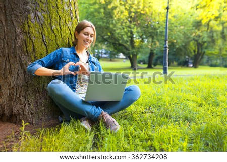 Young woman chatting in the park using laptop.